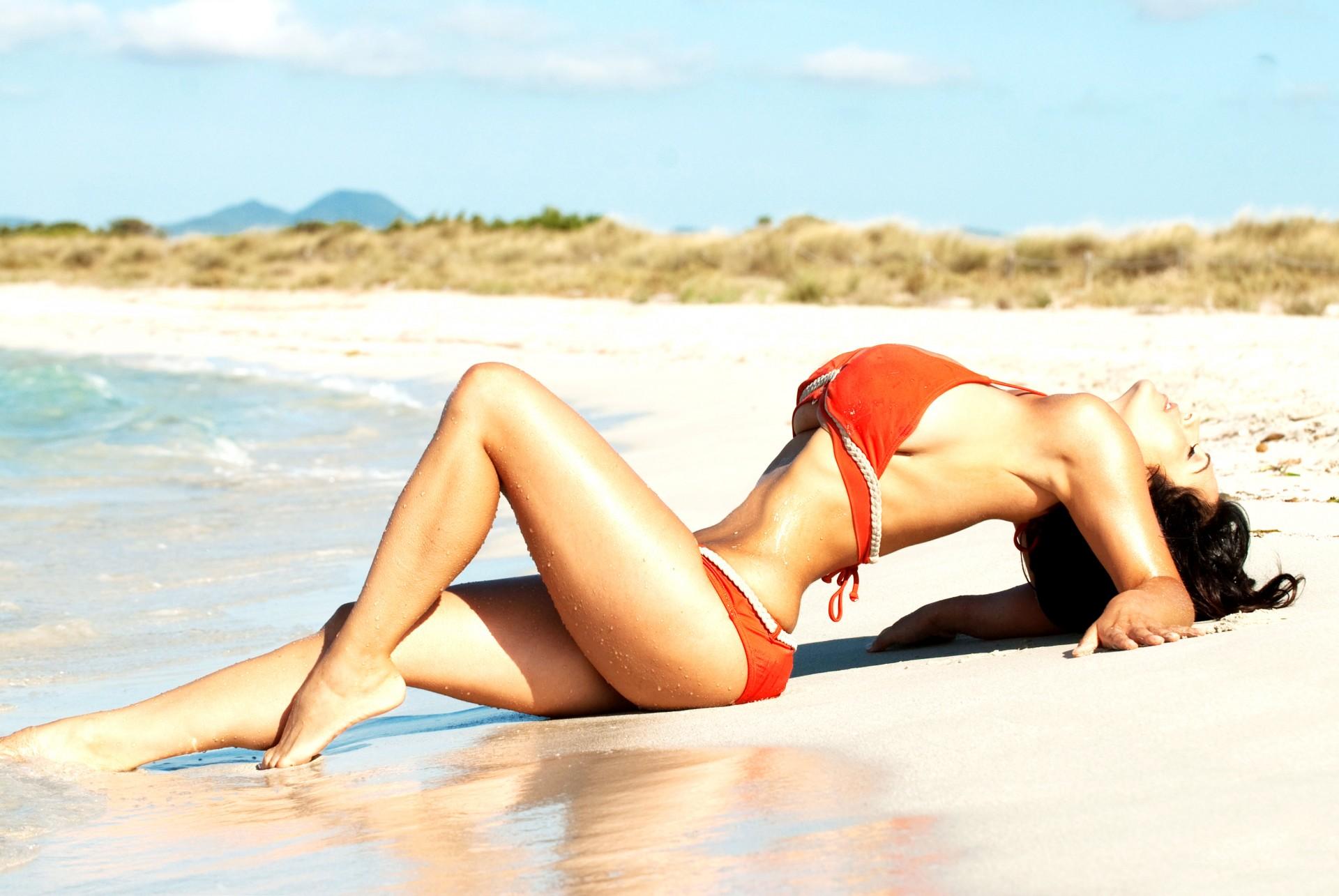 Девушка в красном купальнике на пляже фото