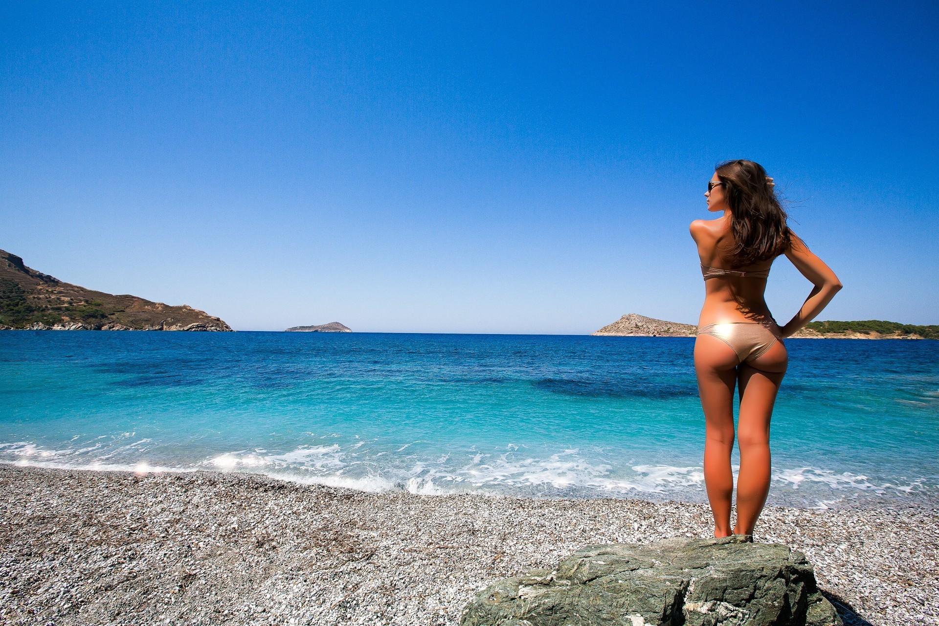 Обнаженная девушка получает загар возле моря  320932