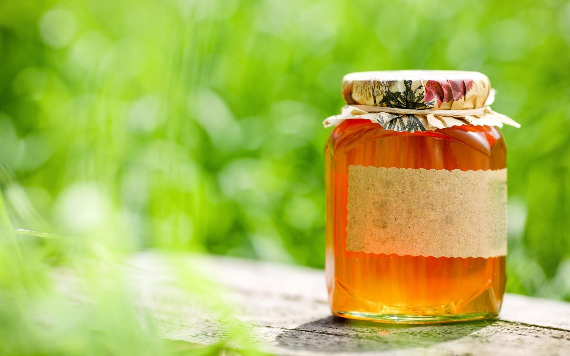 мед в стеклянной баночке на фоне природы