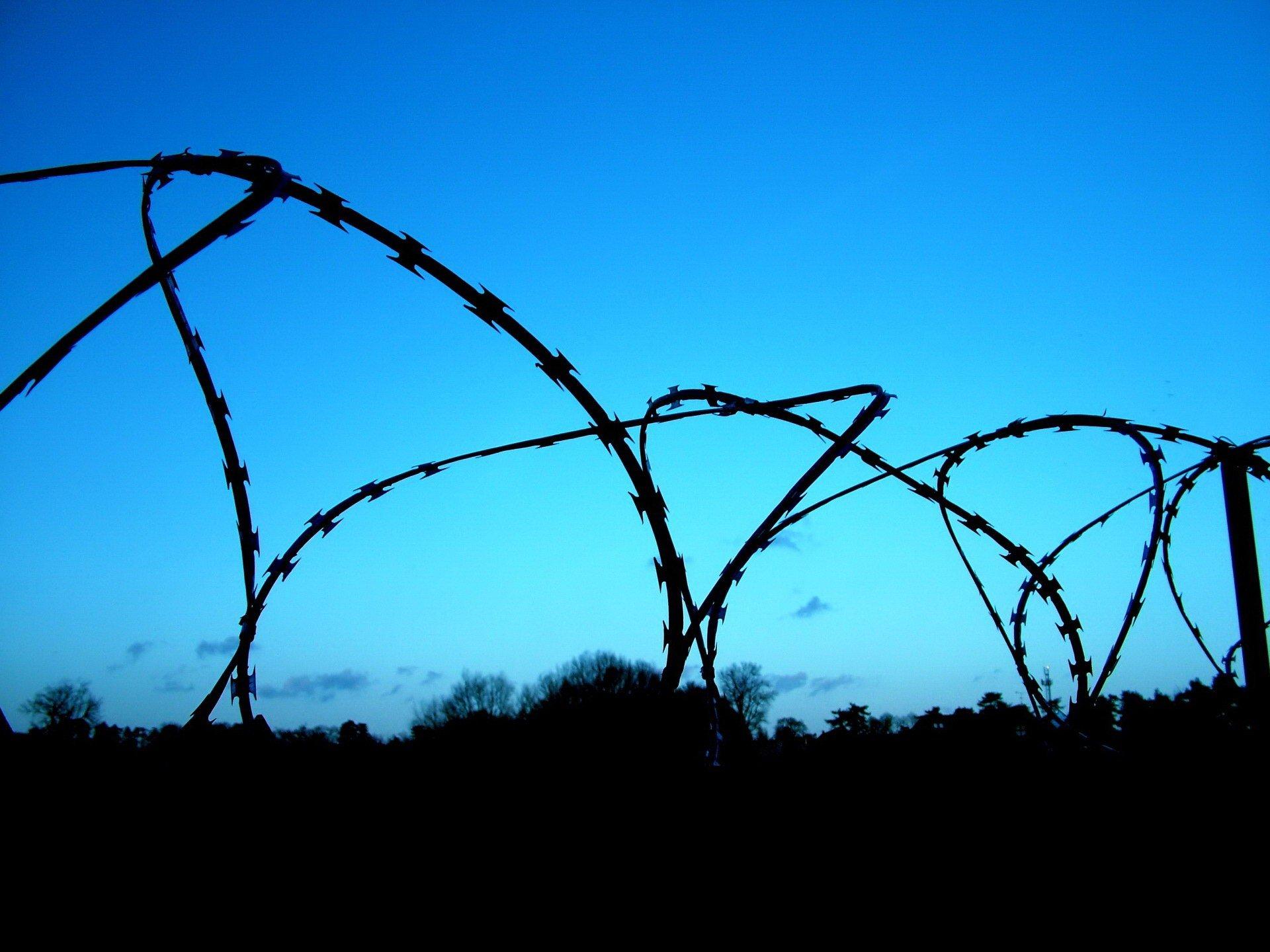Колючая проволка на заборе  № 1701830  скачать