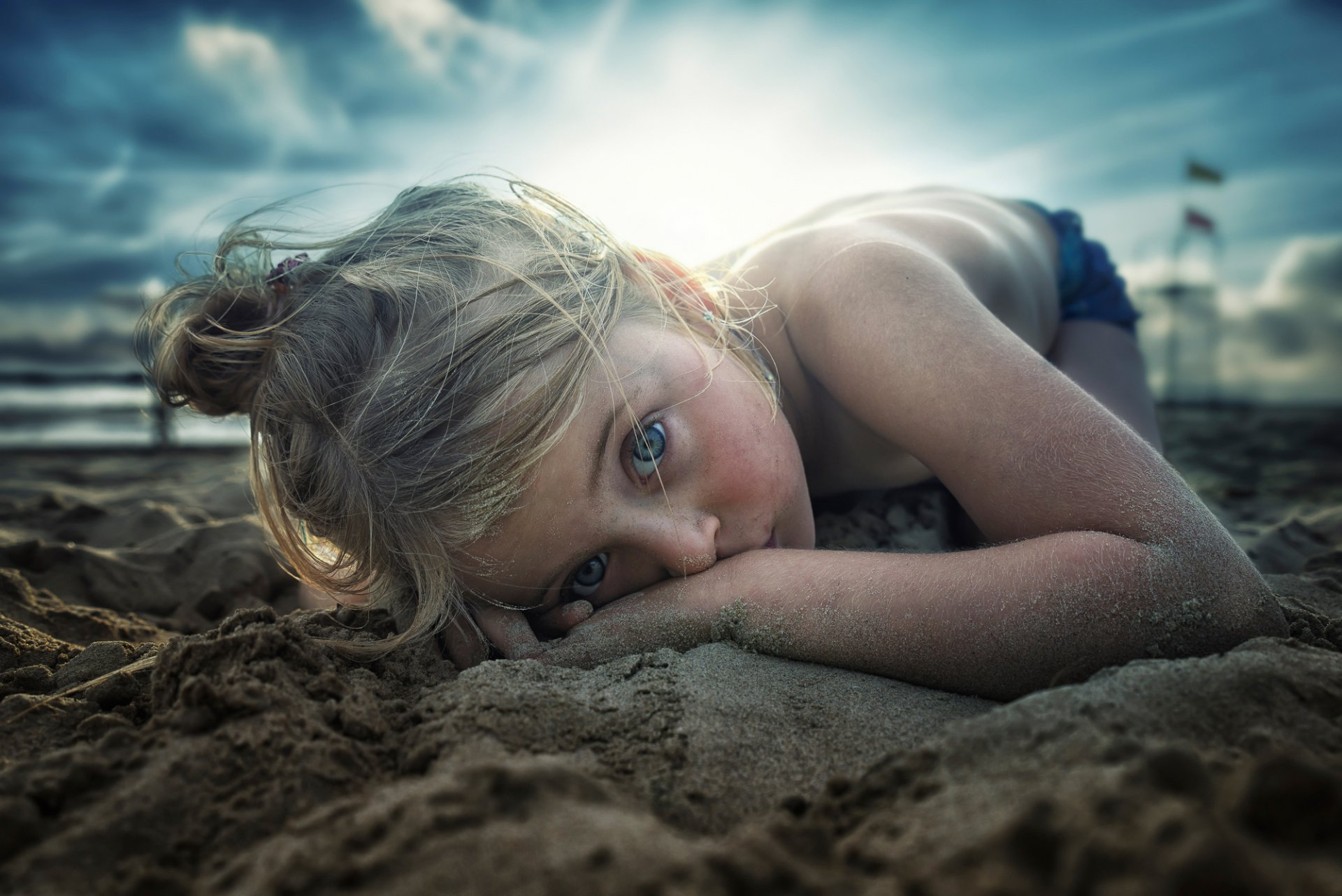 девушка зеленые глаза на песке фото