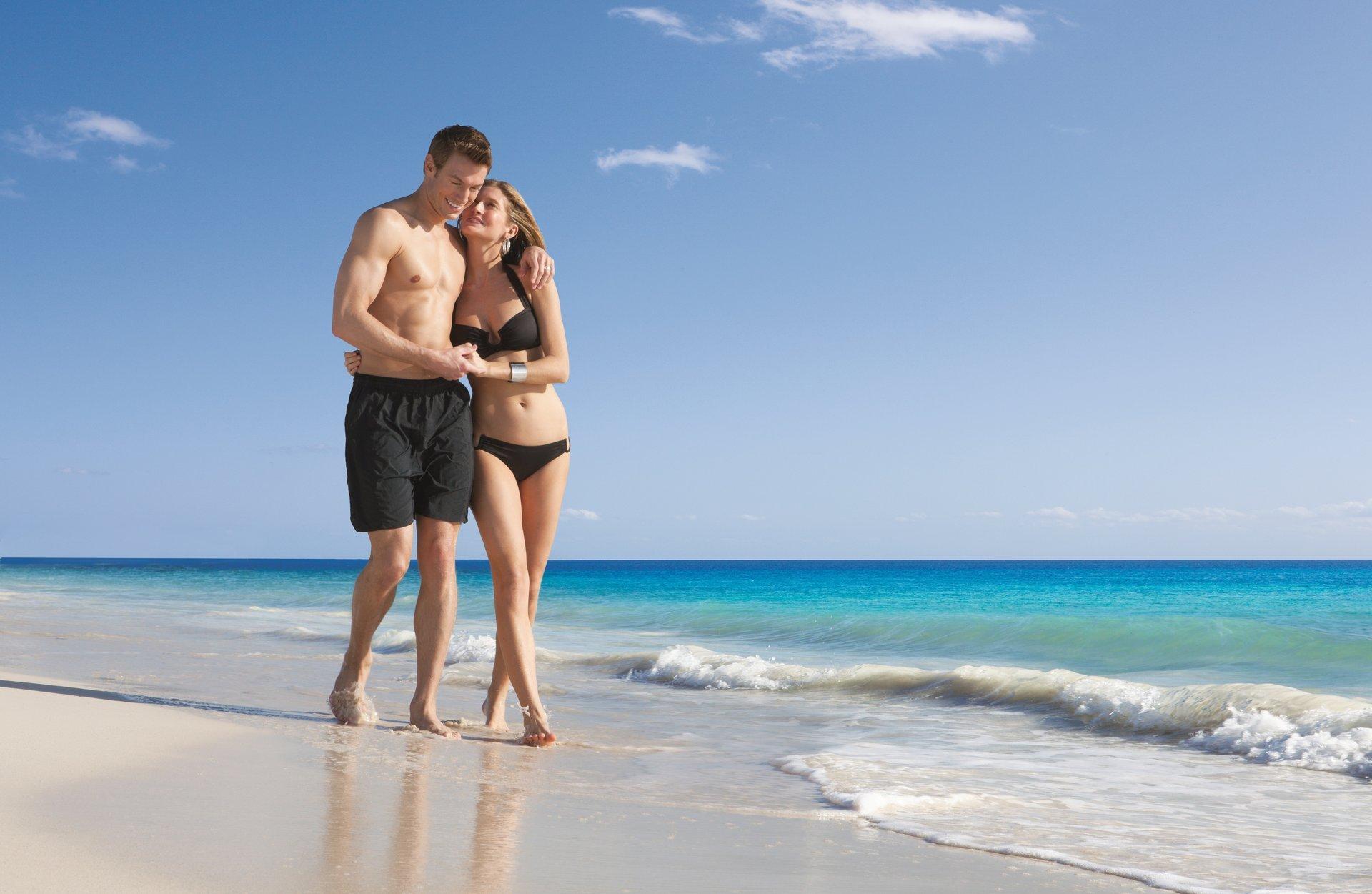 Двое мужчин и девушка на берегу океана