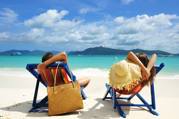 Vacation relax couple man woman boy girl people beach sand sea water sky clouds islands beach chairs bag hat summer boats tropical landscape nature holiday