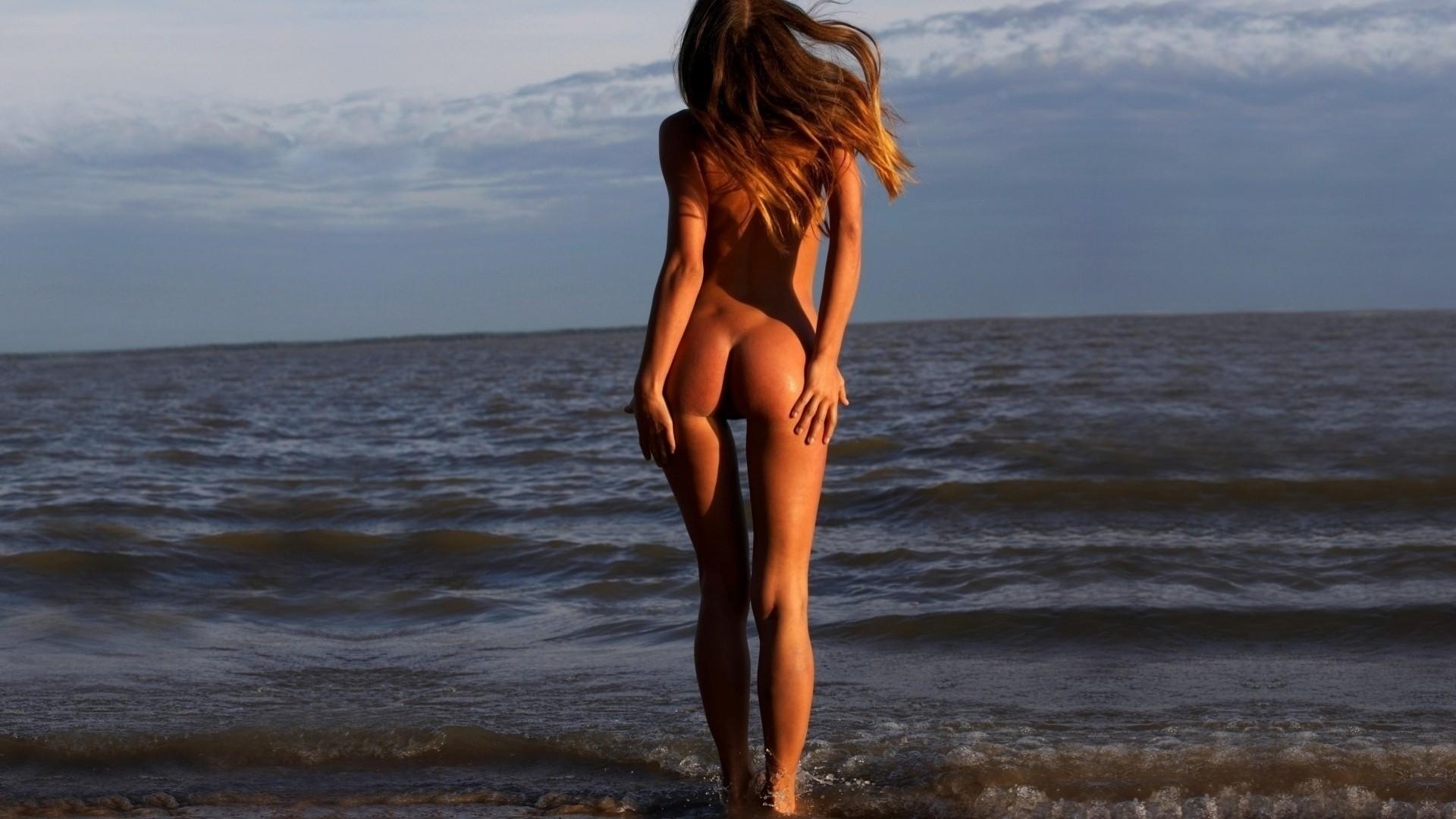Обнаженная женская спина сзади на пляже фото